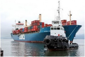 rebocador portuário em manobra com navio contêneiro no porto de Paranaguá