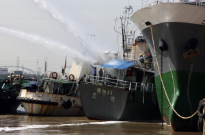 Rescuers spray water onto an oil tanker after an explosion in Ningbo